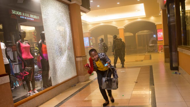 A woman who had been hiding during the gun battle runs for cover after armed police, background, enter the Westgate Mall in Nairobi, Kenya.