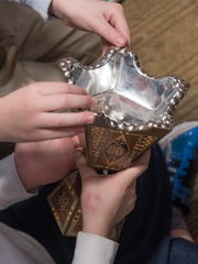 Second grade students hold a vessel used during the month of Ramadan.