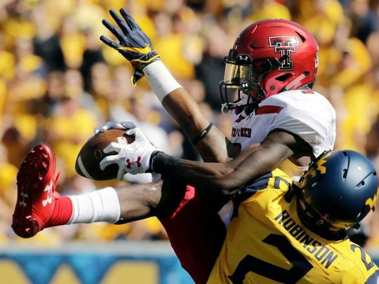 Tech wide receiver T.J. Vasher catches a 53-yard touchdown pass Saturday in a loss to West Virginia.