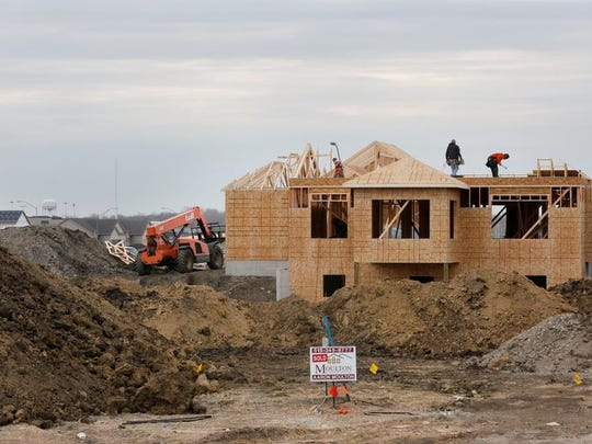 Crews work on a Classic Builders home under construction at Centennial Pointe on the north side of Ankeny in 2014.