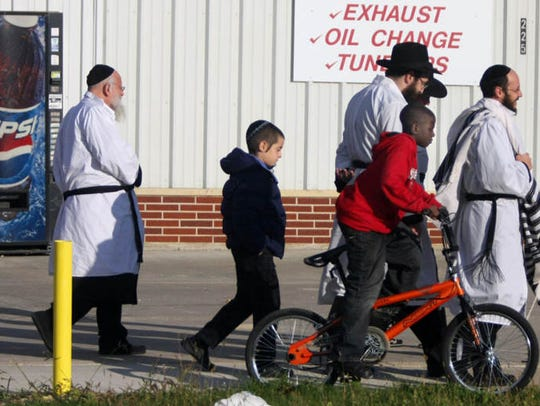 A Somali youth rides his bicycle past a group of Jewish