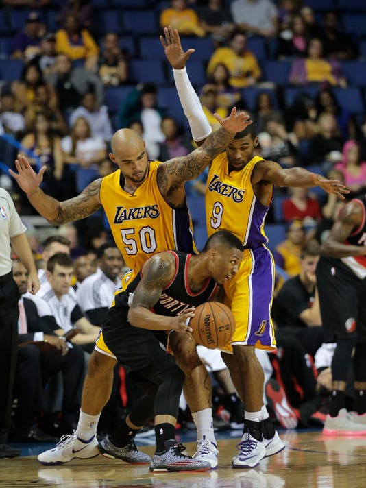 Portland Trail Blazers' Damian Lillard, bottom, is defended by Los Angeles Lakers' Robert Sacre, left, and Ronnie Price during the first half of a preseason NBA basketball game Wednesday, Oct. 22, 2014, in Ontario, Calif. (AP Photo/Jae C. Hong)