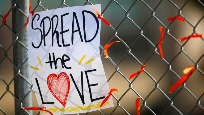 Orange ribbons adorn a fence along with a sign left by students after a walkout to protest gun violence on the soccer field behind Columbine High School Wednesday, March 14, 2018, in Littleton, Colo. More than 250 students took part in the short protest at Columbine, the scene of a mass school shooting on April 20, 1999. (AP Phoot/David Zalubowski)
