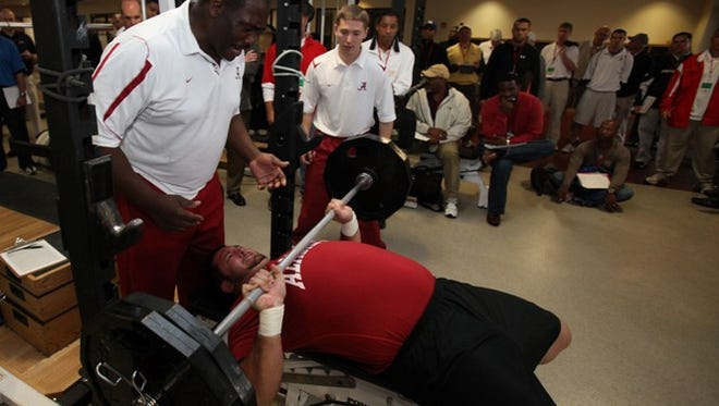 Mike Johnson works out for NFL scouts at Alabama's Pro Day in 2010 with help from strength and conditioning coach Terry Jones.