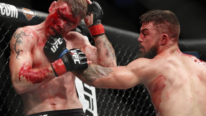 Mike Perry, right, hits Paul Felder during a welterweight mixed martial arts bout at UFC 226, Saturday, July 7, 2018, in Las Vegas.