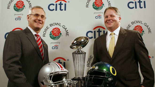 Ohio State coach Jim Tressel (left) and Oregon coach Chip Kelly pose in December 2009 with the Leishman Trophy, which is presented to the winning team in the Rose Bowl.