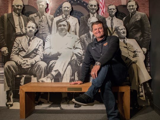 Trevor Hoffman poses for photographers in front of images of baseball greats during his orientation tour of the National Baseball Hall of Fame and Museum, Wednesday, April. 4, 2018, in Cooperstown, N.Y., where he was visiting to prepare for his induction this summer.  (Milo Stewart Jr./National Baseball Hall of Fame and Museum via AP)