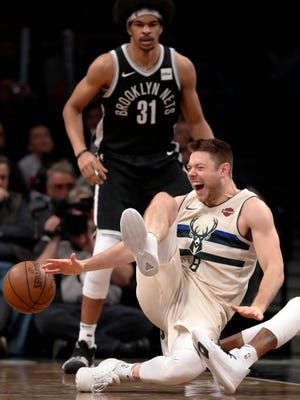 Bucks guard Matthew Dellavedova falls to the floor in pain after spraining his ankle against the Nets on Sunday. Dellavedova flew back to Milwaukee on Monday for a further evaluation on his injured right ankle.