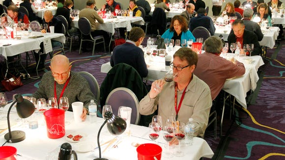 Richard Allen of Webster, front right, and 75 judges from 16 countries and 11 states take in the task of judging 3,756 wines from 20 different countries, all 50 states,\ and six Canadian provinces during the 14th annual Finger Lakes International Wine Competition at the Rochester Plaza in Rochester Sunday afternoon, March 30, 2014.