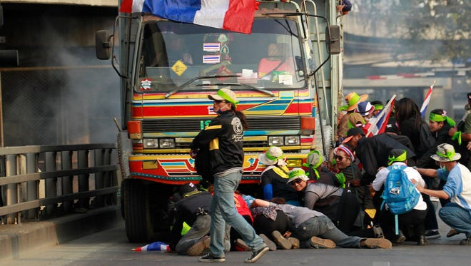 Anti-government protesters take cover near a truck after hearing gunshots during a clash with a pro-government group in Bangkok on Feb. 1, 2014.
