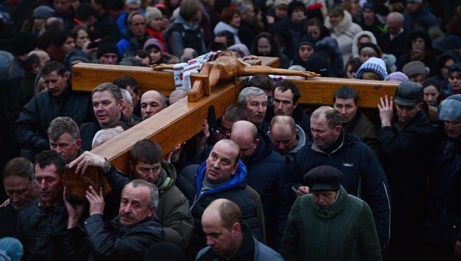 Men carry a cross of the crucifixion to points where anti-government demonstrators were killed in clashes with police in February in Kiev, Ukraine.