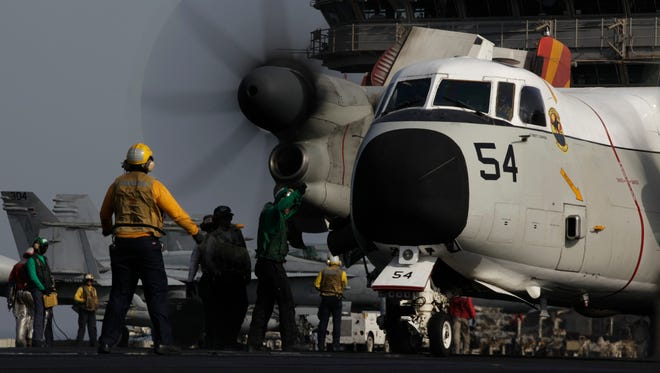 Sailors guide a military plane on the flight deck of the U.S. Navy aircraft carrier USS George H.W. Bush on Aug. 10 in the Persian Gulf.