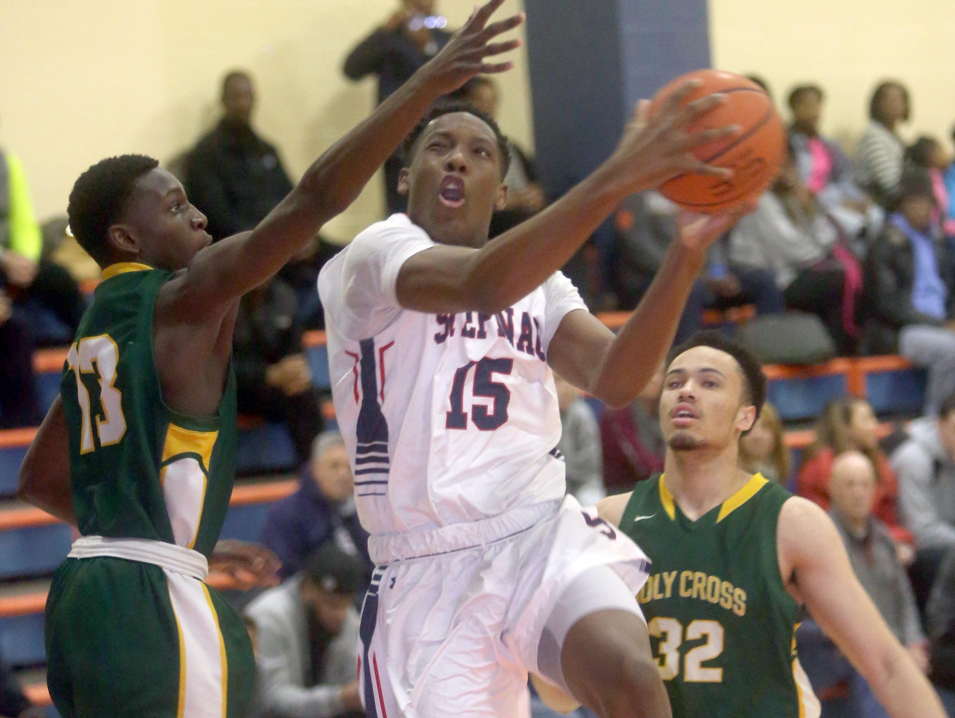 Stepinac's Aundre Hyatt splits Holy Cross defenders during a CHSAA second round AA playoff basketball game against St. Peter's at St. Raymond High School in the Bronx March 3, 2016.