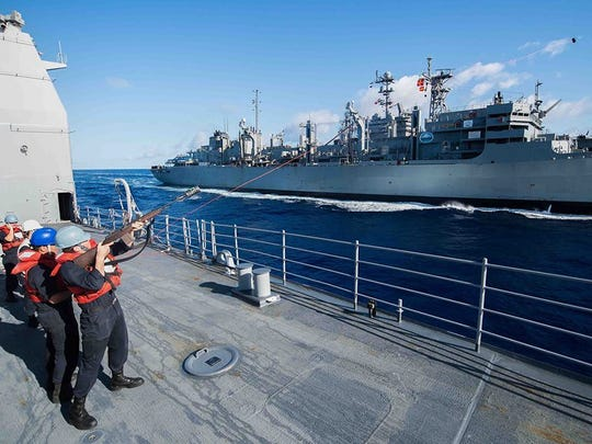 Gunner's Mate 3rd Class Maxwell Reynolds, from Palm Springs, Calif. fires a shot line during a replenishment-at-sea between the guided-missile cruiser USS Mobile Bay (CG 53) and the fast combat support ship USNS Rainier (T-AOE 7).