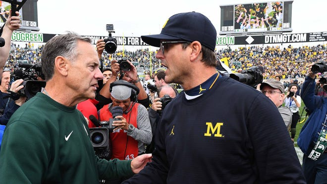 Oct 29, 2016; East Lansing, MI, USA; Michigan State Spartans head coach Mark Dantonio (left) shakes hands with Michigan Wolverines head coach Jim Harbaugh after the Wolverines won, 32-23.