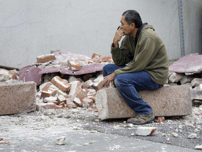 Ron Peralez, of Vacaville, Calif., sits on rubble and looks at earthquake-damaged buildings Aug. 25 in Napa, Calif.
