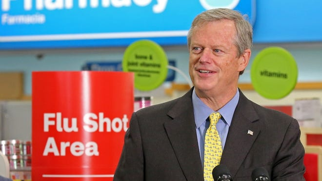 Gov. Charlie Baker speaks to reporters Thursday at a CVS Pharmacy in Roslindale after getting a flu vaccine.
