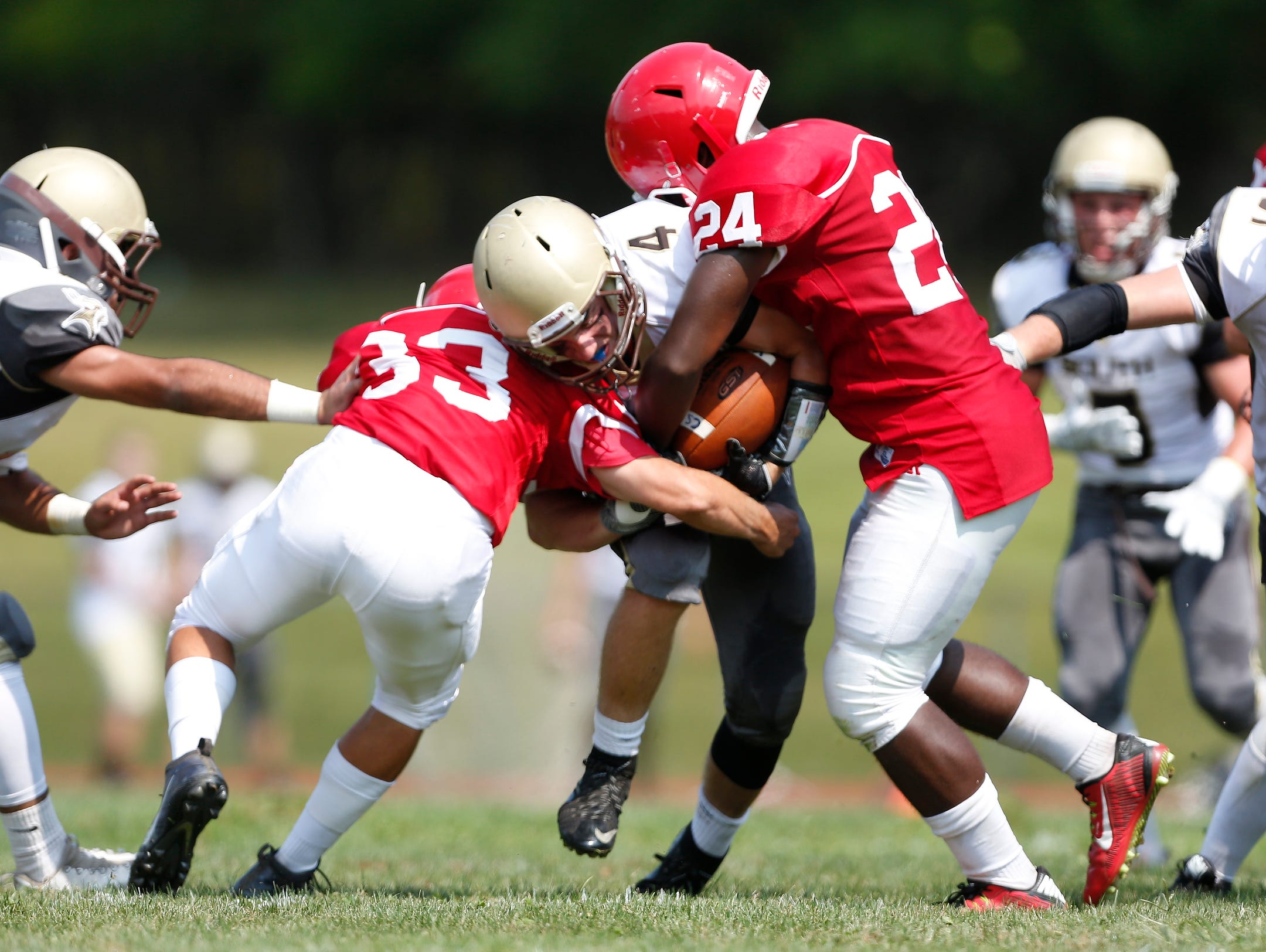 Clarkstown South running back Kyle Samuels (4) is tackled by North Rockland's Mike Csernecky (33) and Justin Graham (24) during football action at North Rockland High School in Thiells on Saturday, September 10, 2016. The game second half is postponed due to heat. Clarkstown South is up at the half, 17-0.