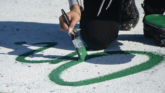 Battle Creek Central senior Damaris Chavez, 17, puts the finishing touches on her Michigan State University-themed parking spot Sunday near the high school in Battle Creek.