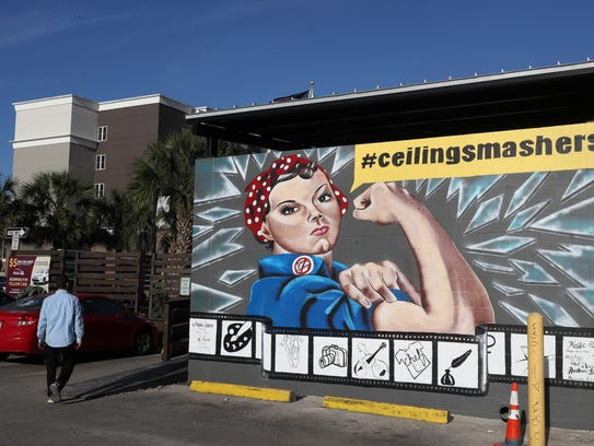"""Kollet Probst, along with elleBelle Photography's Lydia Bell, just finished leading a Rosie the Riveter-themed """"#ceilingsmashers"""" mural, unveiled Wednesday, at the Garages on Gaines Street in honor of Women's History Month. The mural is a tribute to women's accomplishments, featuring seven Tallahassee-based women in artistic professions, including a chef, a dancer, a musician, a stylist and a writer."""