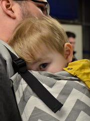 Micah Adams, 1 year old, looks out from his position