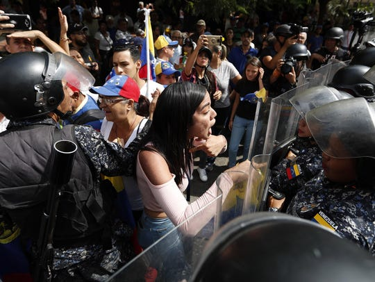 A woman confronts Venezuelan police blocking a crowd