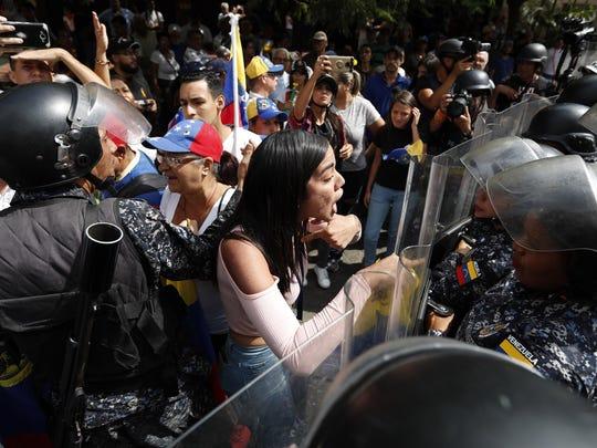 A woman confronts Venezuelan police blocking a crowd