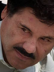 """Joaquin """"El Chapo"""" Guzman is escorted to a helicopter in handcuffs by Mexican Navy marines in 2014."""