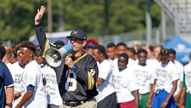 Jim Harbaugh works at a camp at Pearl High School in Pearl, Miss.