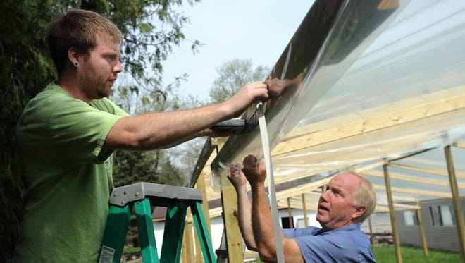 Rusty Ortman, left, and his father, Tom Ortman, set up a structure to cover the pumpkin patch April 19 at the Ortman Family Greenhouse. The plastic needs to be pulled completely tight so rain water doesn't collect on the top.