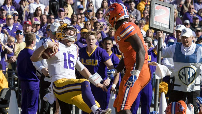 LSU quarterback Danny Etling (16) is knocked out of bounds by Florida Gators linebacker Vosean Joseph (11) during the second half at Tiger Stadium.