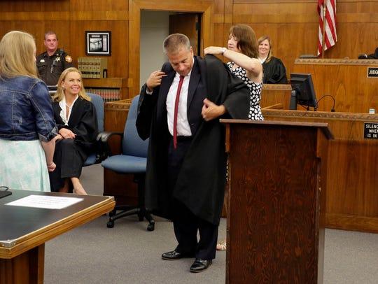 Cathy Hoffmann, presents the robe onto Kent Hoffmann,