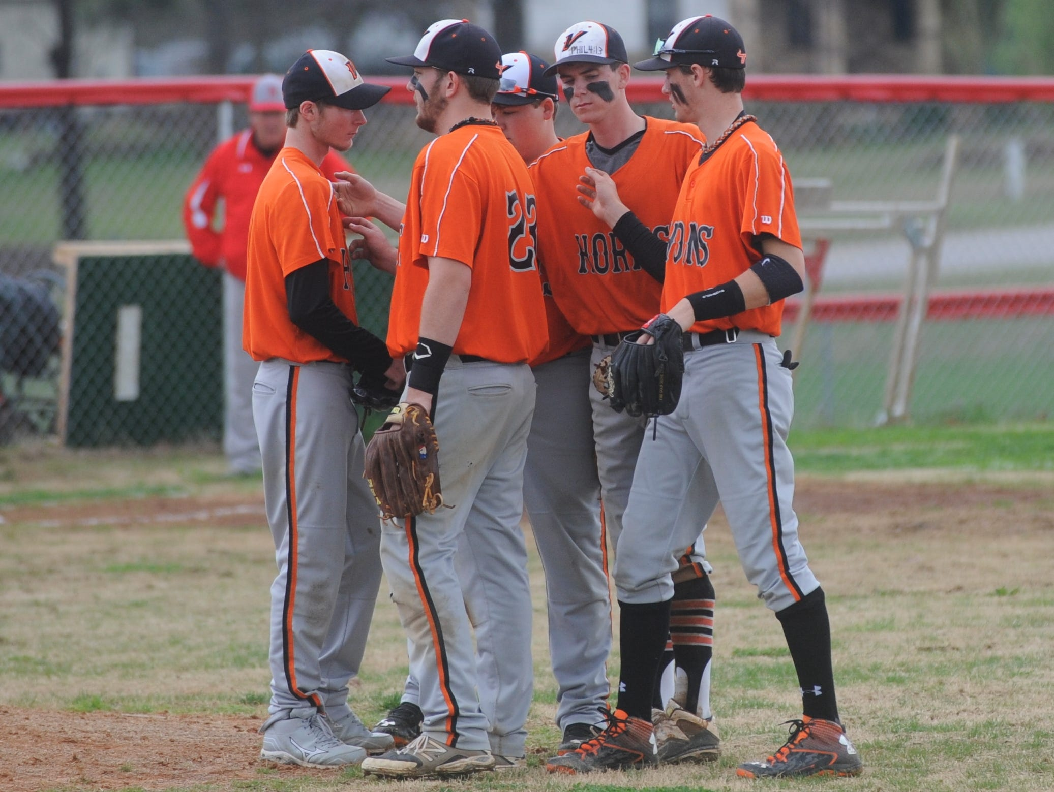 Several of the Viola Longhorns meet before an inning against Norfork earlier this season.