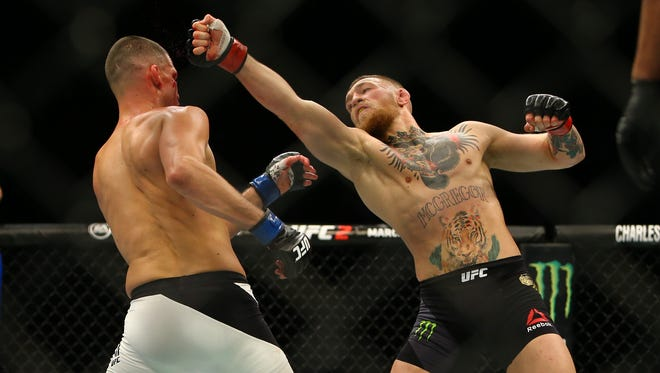 Conor McGregor (R) punches Nate Diaz during UFC 196 at the MGM Grand Garden Arena on March 5, 2016 in Las Vegas.