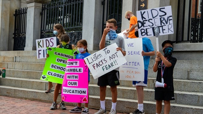 Children stand outside the Statehouse holding signs Wednesday as parents rally for an in-person education in the fall.