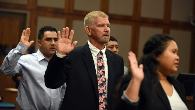 Shane Harold Kleynhans from Zambia, middle, is sworn in as an American citizen during the naturalization ceremony Thursday at the William M. Colmer Federal Building. District Judge Keith Starrett swore in 13 new American citizens.