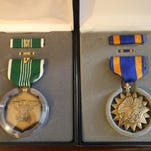 In additon to a Purple Heart, a box with a soldier's name on it contains these two medals: An Army Commendation Medal, with a Valor Device (left) and an Air Medal.
