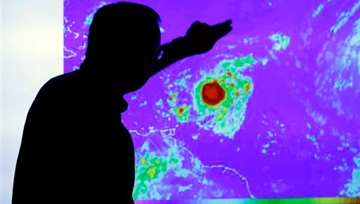 James Franklin, chief hurricane forecaster, looks at an image of Tropical Storm Erika as it moves westward toward islands in the eastern Caribbean at the National Hurricane Center on Wednesday.