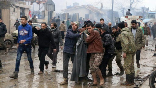 Rescue workers attend to those injured after they and Syria's opposition activists say dozens were killed when a car bomb went off in a busy market in a rebel-held Syrian town of Azaz along the Turkish border, Saturday, Jan. 7, 2017 . The Syrian Observatory for Human Rights monitoring group says the explosion Saturday was caused by a rigged water or fuel tanker, which explains the large blast and high death toll.