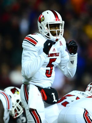 Louisville Cardinals quarterback Teddy Bridgewater (5) gestures at the line of scrimmage during the first quarter against the Cincinnati Bearcats at Nippert Stadium.
