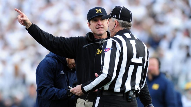 Michigan coach Jim Harbaugh talks to an official during the win over Penn State on Saturday.