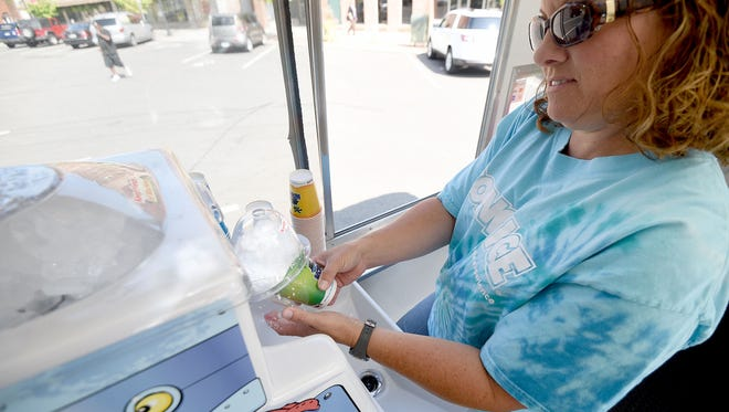 April Prosser makes shaved ice from her Kona Ice food truck on Thursday in Central Park.
