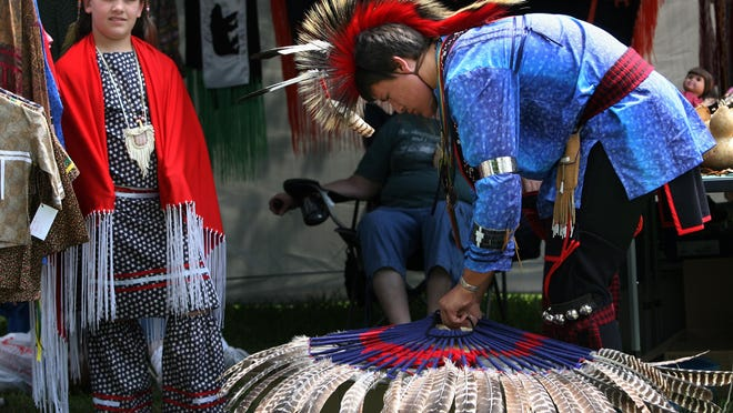 A participant prepares for the grand entry dance at the Gathering of Great Lakes Nations Pow Wow in 2009.