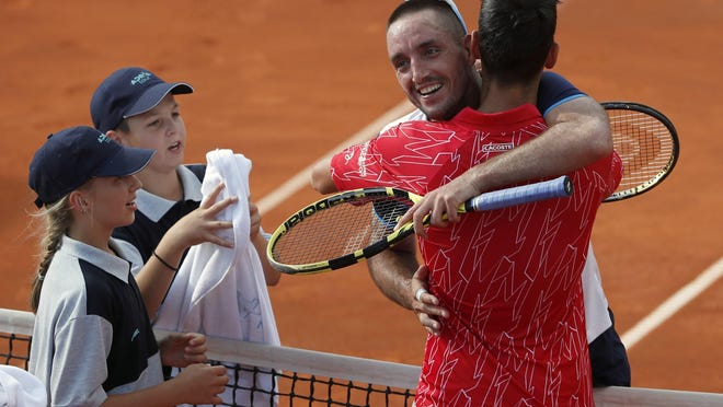 In this Saturday, June 13, 2020 photo, Serbia's Novak Djokovic, front right, hugs with Serbia's Viktor Troicki after their match of the Adria Tour charity tournament in Belgrade, Serbia. Novak Djokovic has tested positive for the coronavirus after taking part in a tennis exhibition series he organized in Serbia and Croatia. The top-ranked Serb is the fourth player to test positive for the virus after first playing in Belgrade and then again last weekend in Zadar, Croatia. Viktor Troicki said Tuesday that he and his pregnant wife have both been diagnosed with the virus.
