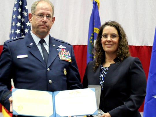 Sharon Landsberry, wife of fallen Sparks Middle School math teacher Michael Landsberry, accepts an award from Brig. Gen. William Burks at the Airman's Medal ceremony in Reno on Sunday, Oct. 19, 2014.