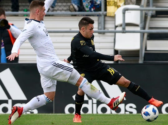 Columbus Crew defender Milton Valenzuela (19) keeps the ball in bounds alongside Vancouver Whitecaps defender Jake Nerwinski (28) in the second half of an MLS soccer game in Columbus, Ohio, Saturday, March 31, 2018. (Brooke LaValley/The Columbus Dispatch via AP)