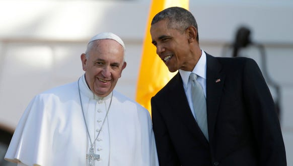 President Barack Obama leans over to talk to Pope Francis