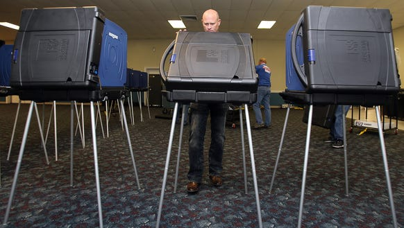 Duane Wright sets up a voting booth on March 3, 2016,