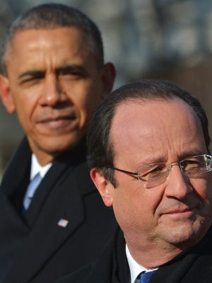 A picture taken Feb. 11, 2014, shows U.S. President Obama, left, and French President Francois Hollande listening to the national anthems during a welcoming ceremony at the White House in Washington.