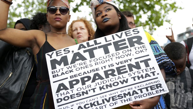 "Two women hold a sign showing why saying ""all lives matter"" misses the point as people gather in Brixton, south London to protest against police brutality in the US, on July 9."